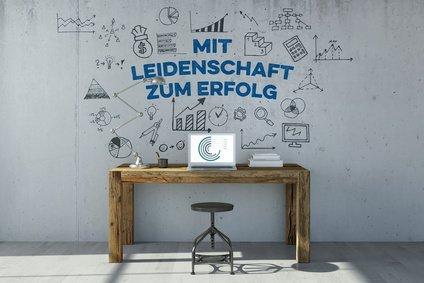 Schreibtisch mit Leidenschaft zum Erfolg als Slogan an der Wand
